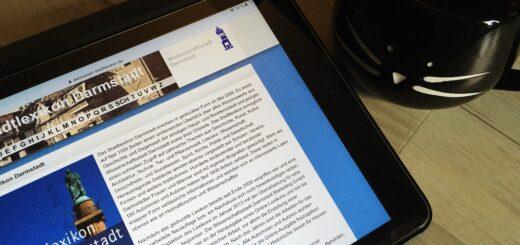 Tablet, auf dem die Startseite des Stadtlexikon Darmstadt geöffnet ist. Daneben eine schwarze Tasse in Katzenform.