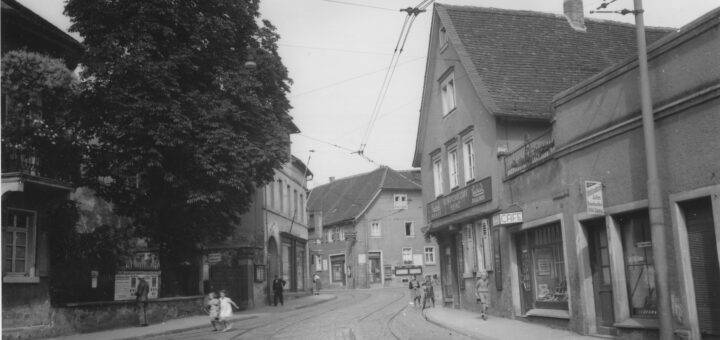 Eine Straße mit darauf verlegten Straßenbahnschienen schlängelt sich durch Häuser in einem Ortskern; links ein Garten mit einem großen Baum, dessen Äste auf die Straße ragen, zwei Kinder darunter rennen über die Straße und sind durch die Bewegung unscharf; rechts ein Café, davor drei Kinder, eines mit einem Fahrrad