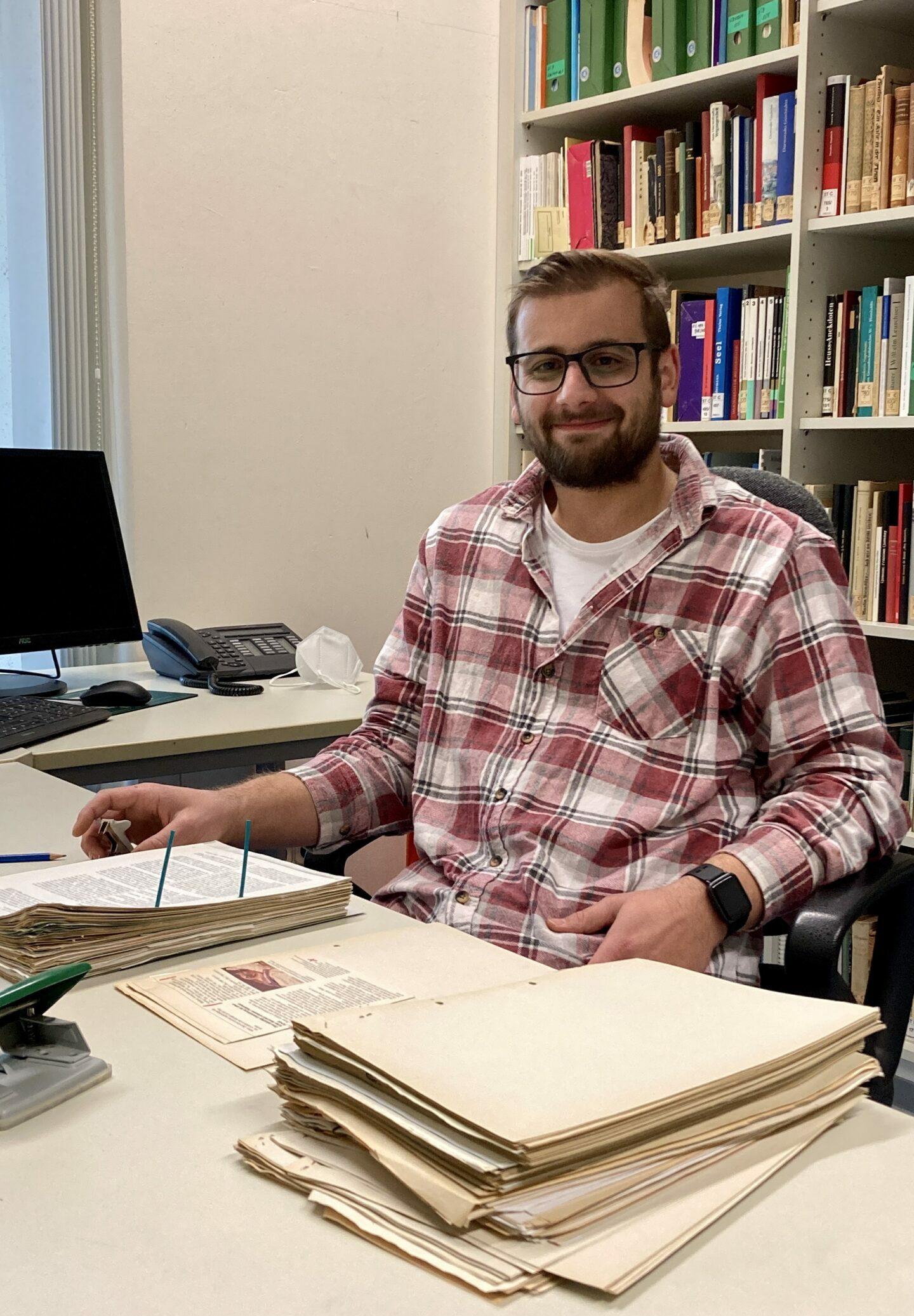 Ein Junger Mann mit Bart und kariertem Hemd sitzt an einem Schreibtisch, vor ihm eine Akte, die gerade umgebettet wird. Im Hintergrund ist ein gefülltes Bücherregal zu sehen.