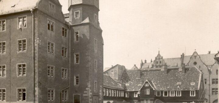 Gebäude der Stadtbibliothek in der Pädagogstraße mit einigen geöffneten Fenstern, davor ein Zaun mit geöffnetem Tor und eine nach rechts abfallende Straße