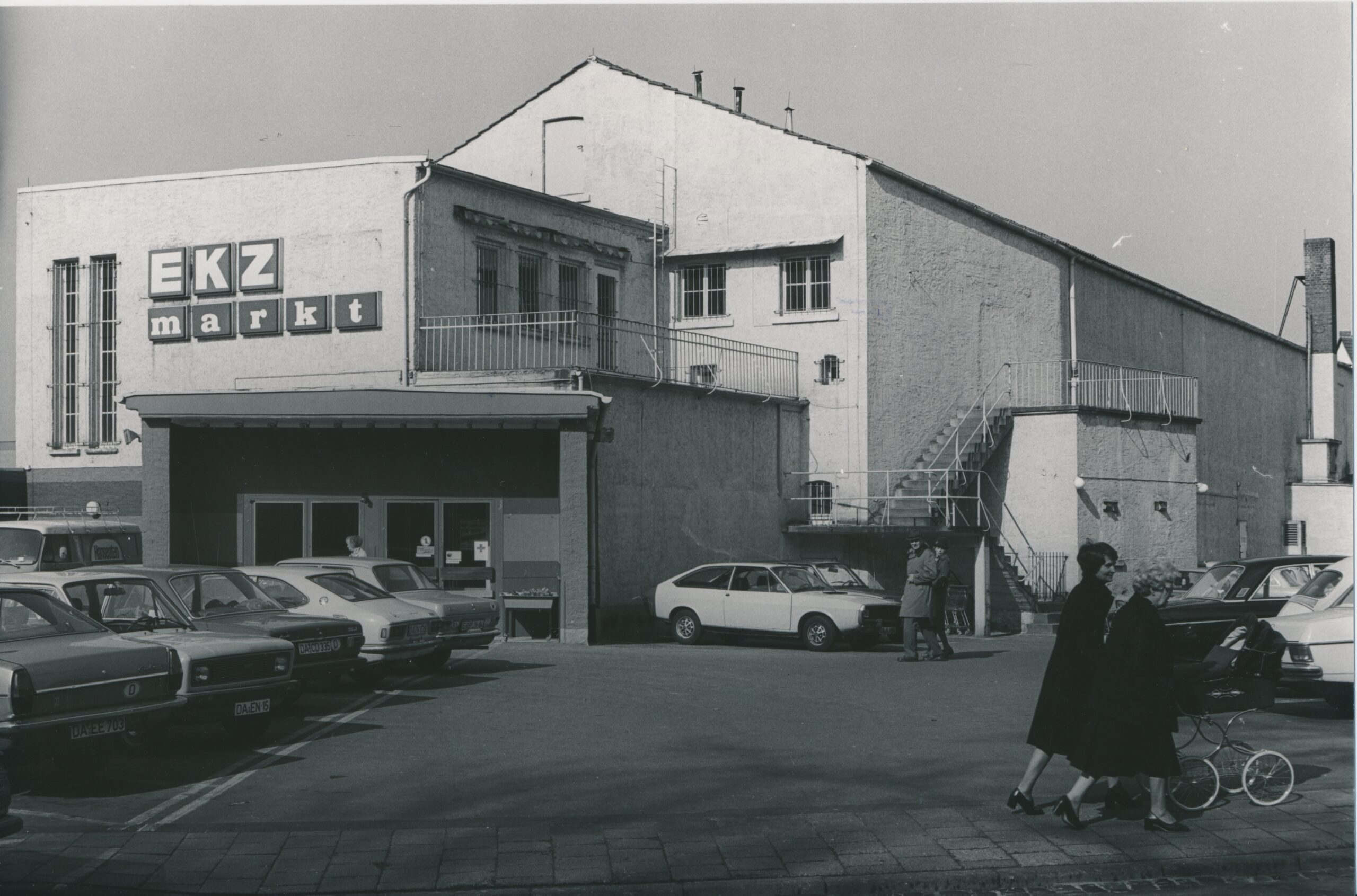 Aufnahme des Einkaufszentrums EKZ markt mit Parkplatz im Vordergrund und zwei Frauen mit Kinderwagen, die nach rechts aus dem Bild laufen
