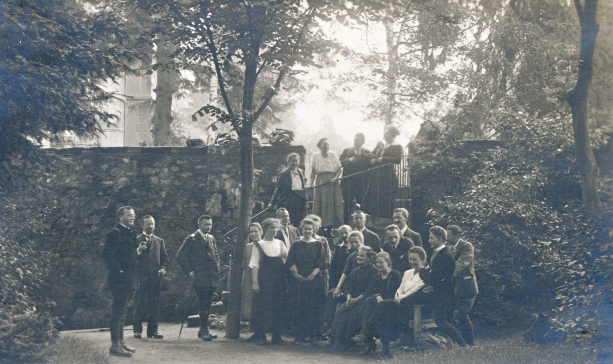22 Personen in Freizeitkleidung stehen in entspannter Haltung vor und auf einer Treppe zu einem Gruppenfoto aufgestellt in einer parkählichen Umgebung.