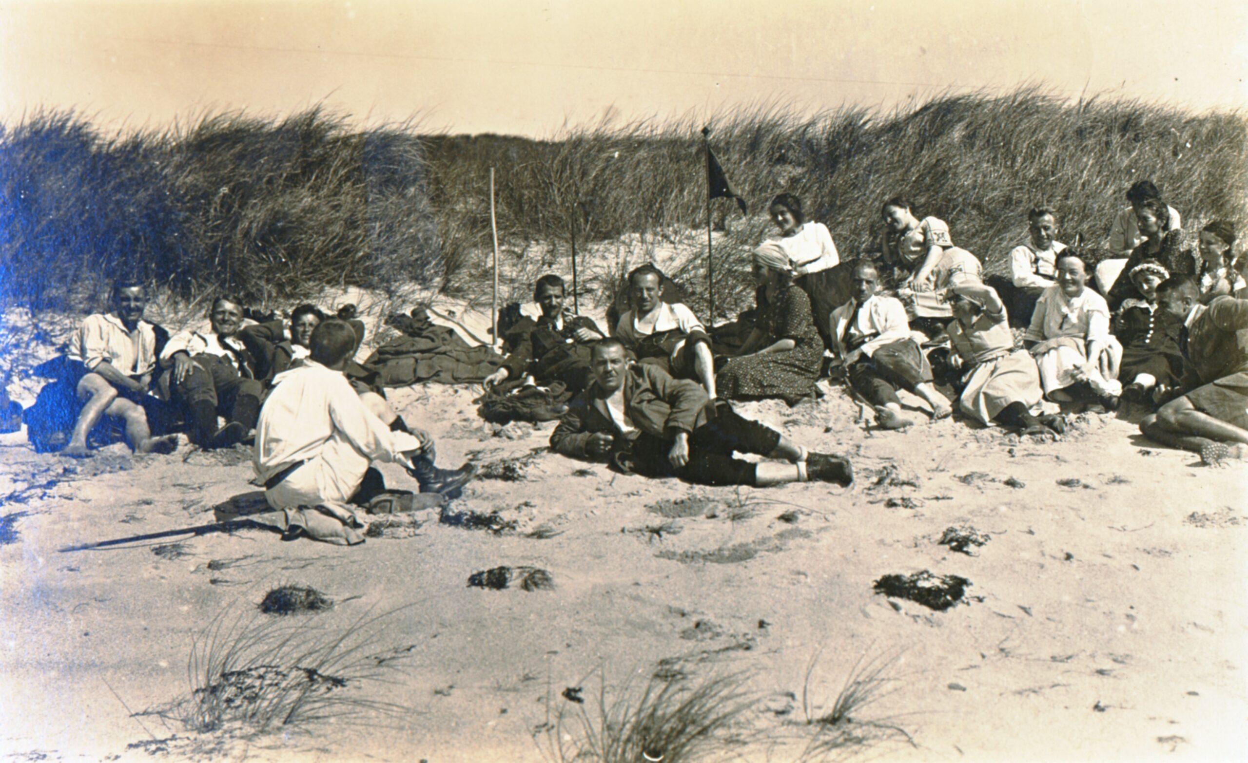19 Personen sitzen und liegen in Freizeitkleidung vor einer Düne im Sandstrand und auf Decken und Jacken, die Stimmung ist ausgelassen.