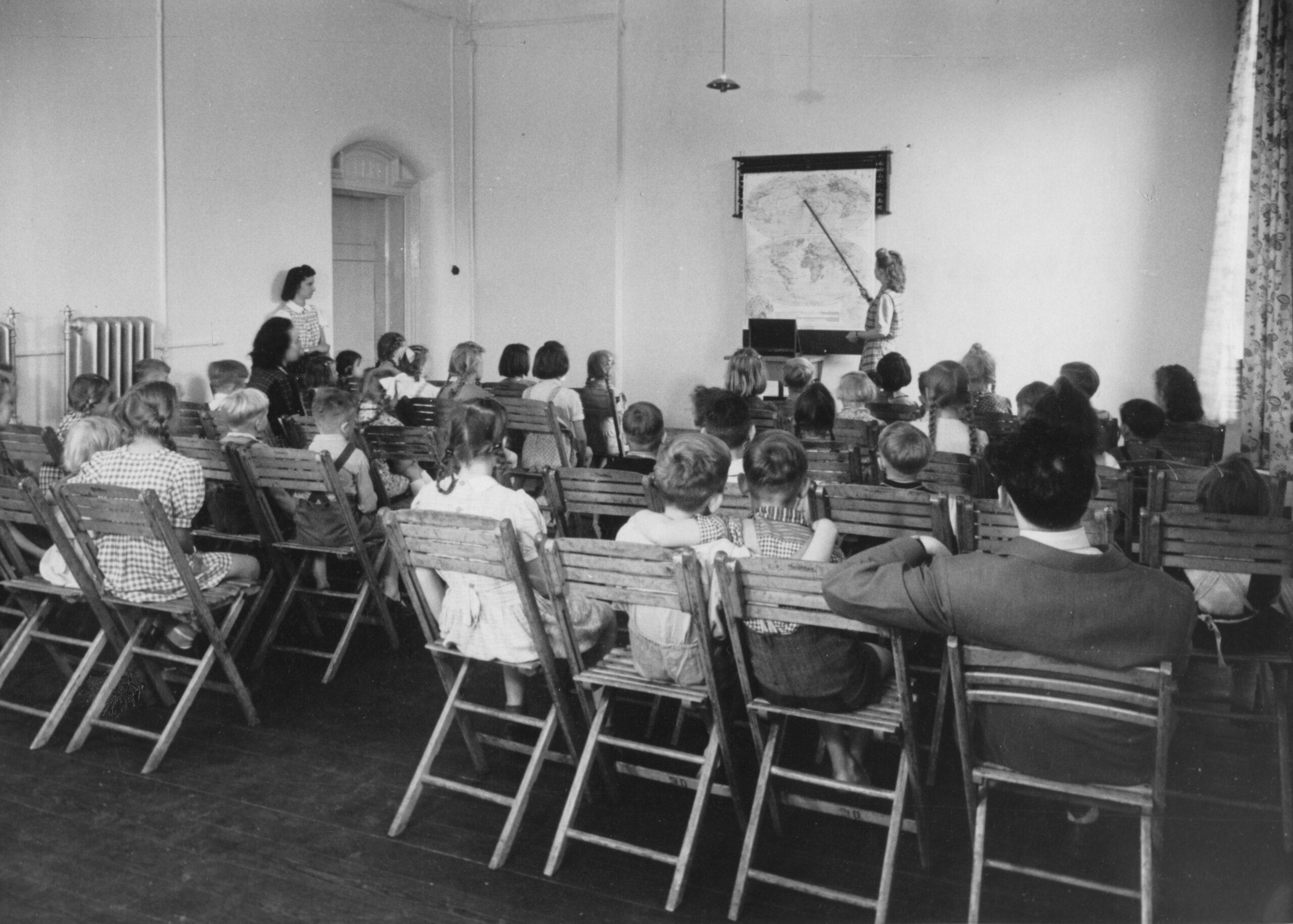 Eien Klasse mit Kindern sitzt auf Klappstühlen aus Holz in einem karg eingerichteten Raum, eine Lehrerin deutet mit einem Zeigestab auf eine an der Wand angebrachte Weltkarte