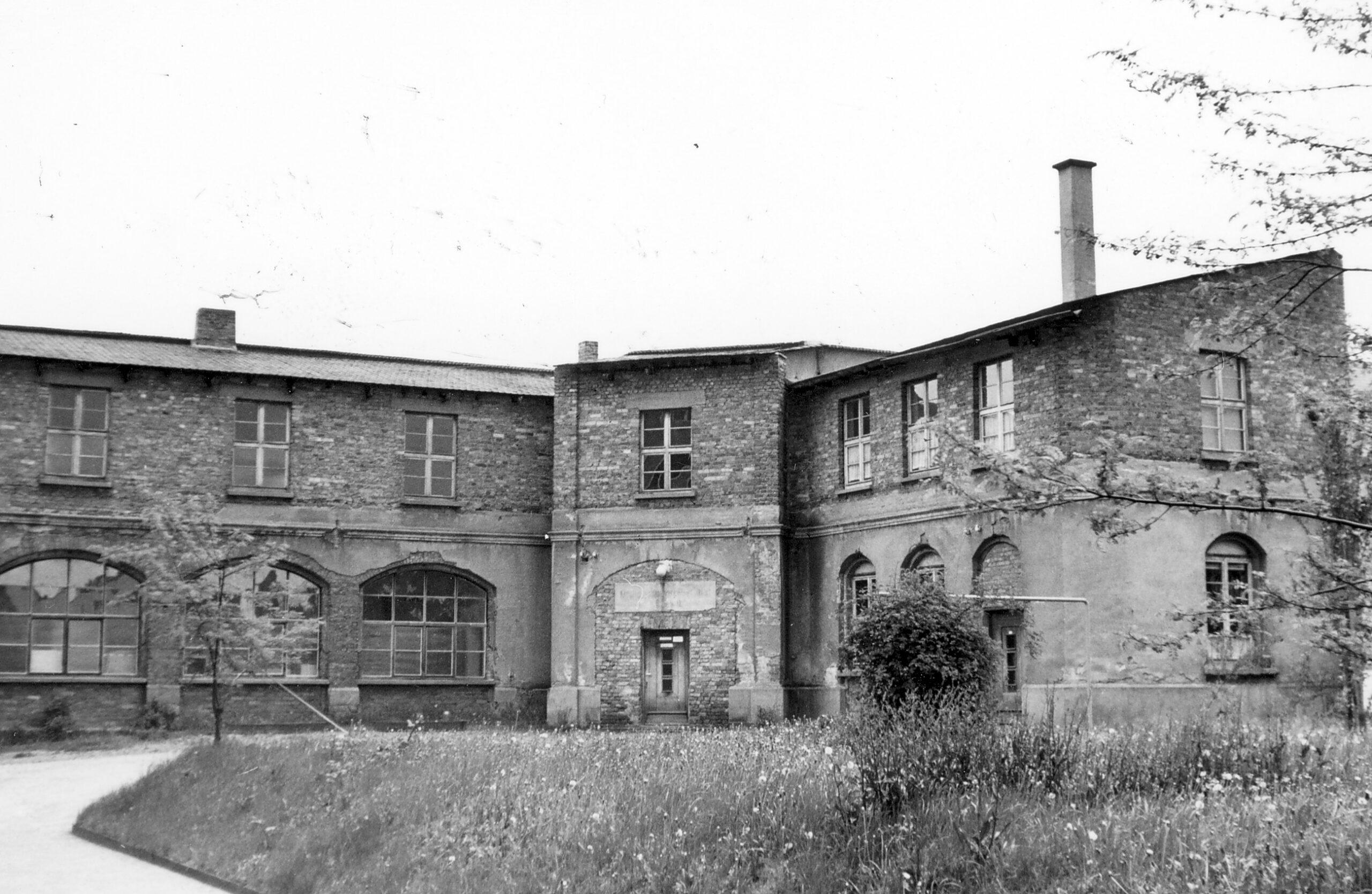 Längliches Gebäude mit großen Fenstern im Erdgeschoss und einer Backsteinfassade, von der teilweise der Putz gebrochen ist