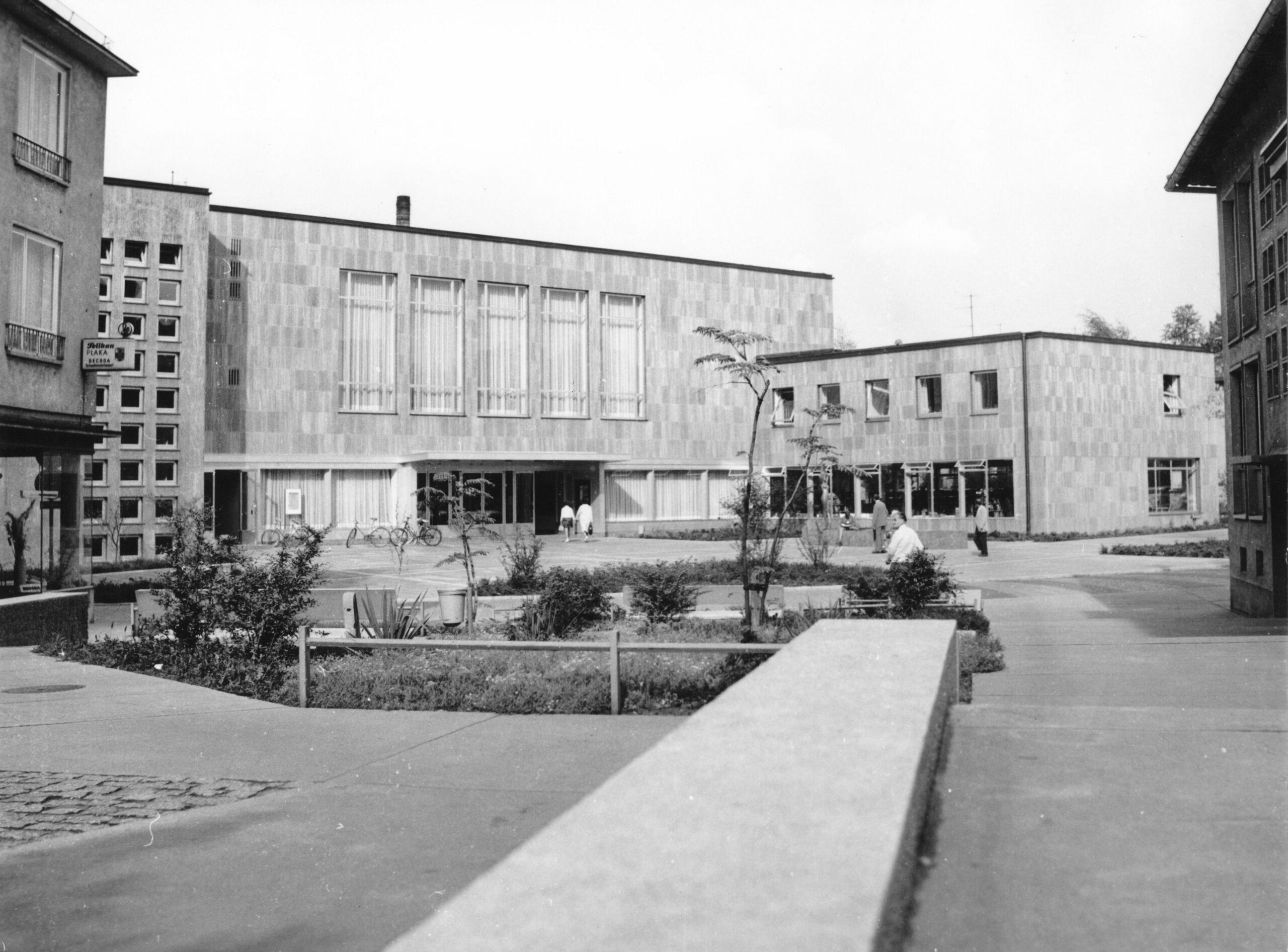 Blick auf den Eingangsbereich des Justus-Liebig-Hauses, im Vordergrund eine Mauer und ein bewachsenes Bett, auf dem Platz vor dem Gebäude einzelne Personen