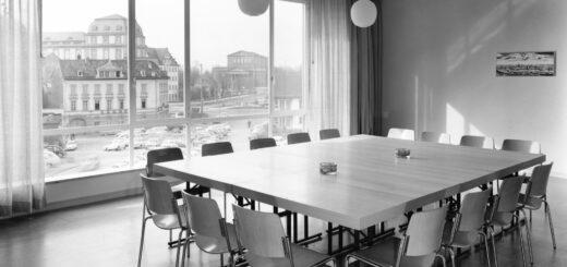 Großer Tisch mit 16 Stühlen, dahinter ein großes Fenster mit Blick auf das Schloss und im Hintergrund das Haus der Geschichte