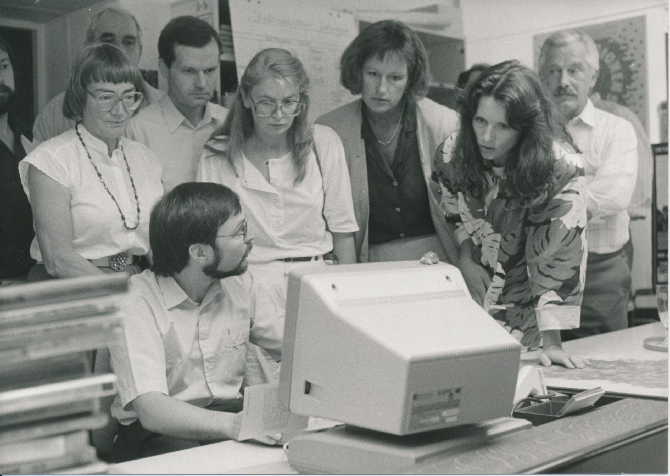 Eine Gruppe von 9 Personen steht hinter einem Mann, der vor einem Computer sitzt; eine Frau beugt sich fragend nach vorne während er ihr zuhört