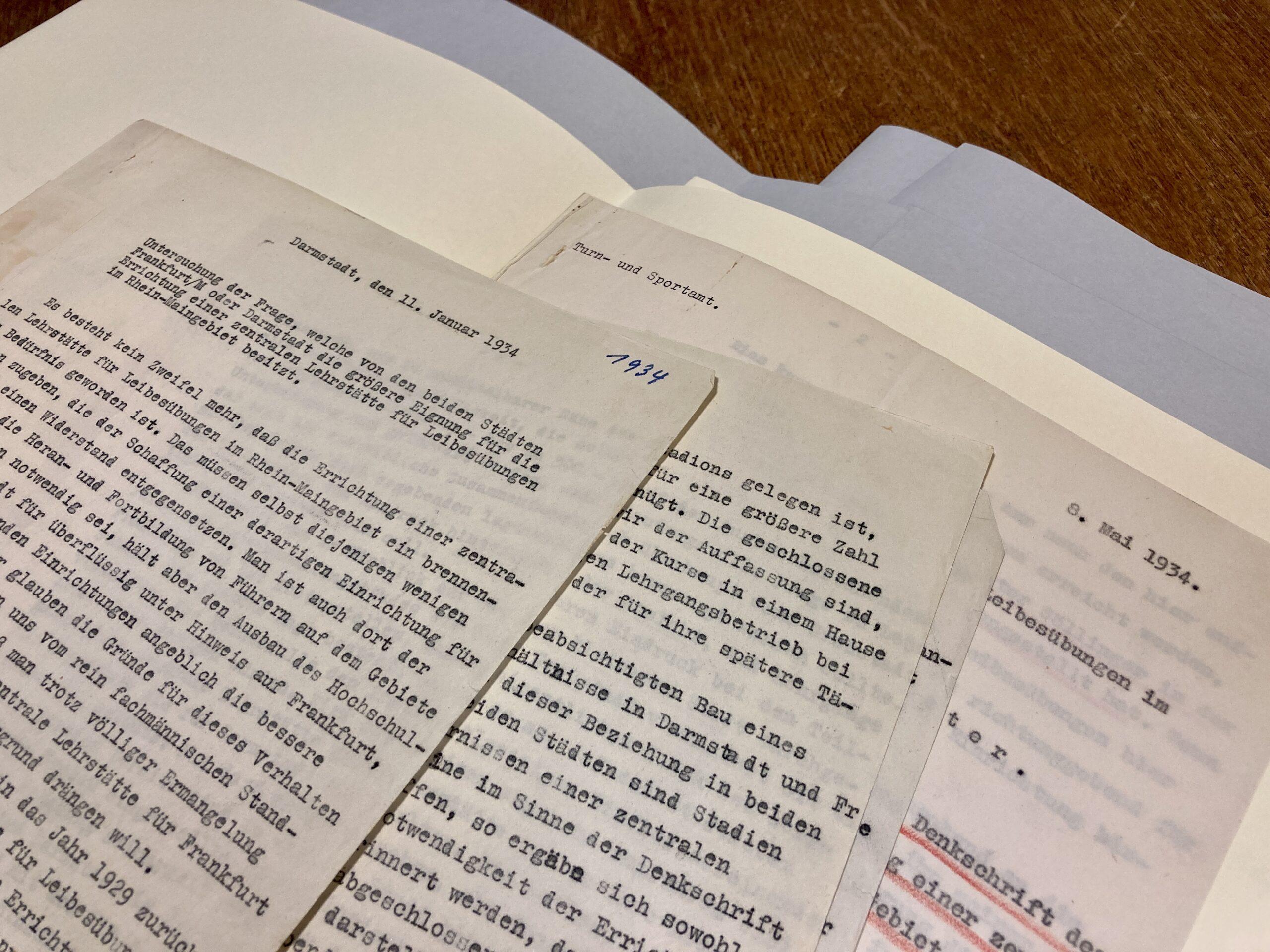 Aufgefächert liegen mehrere Schriftstücke aufeinander. Es ist von jeder Seite nur das obere Drittel zu sehen. Alle Seiten sind mit Schreibmaschine beschriftet. Unter den dünnen Papieren ist archivisches Verpackungsmaterial zu sehen.