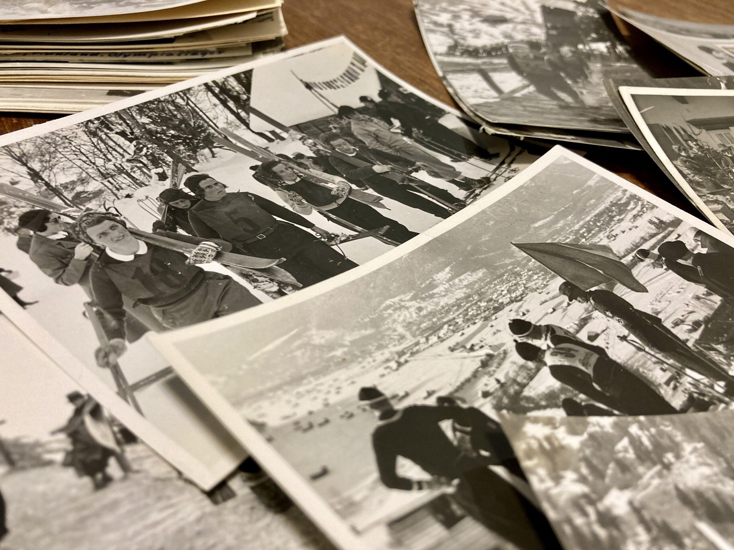 Mehrere schwarz-weiße Fotos liegen übereinander auf einem Holztisch. Das unscharfe Foto im Vordergrund zeigt Menschen in Skisport-Kleidung der 1930er Jahre vor einem verschneiten Tal. Der Fokus des Bildes liegt auf einem Foto im Hintergrund, das mehrere Frauen in Wintersportkleidung und Skiern auf den Schultern auf dem Weg zur Skipiste zeigt.