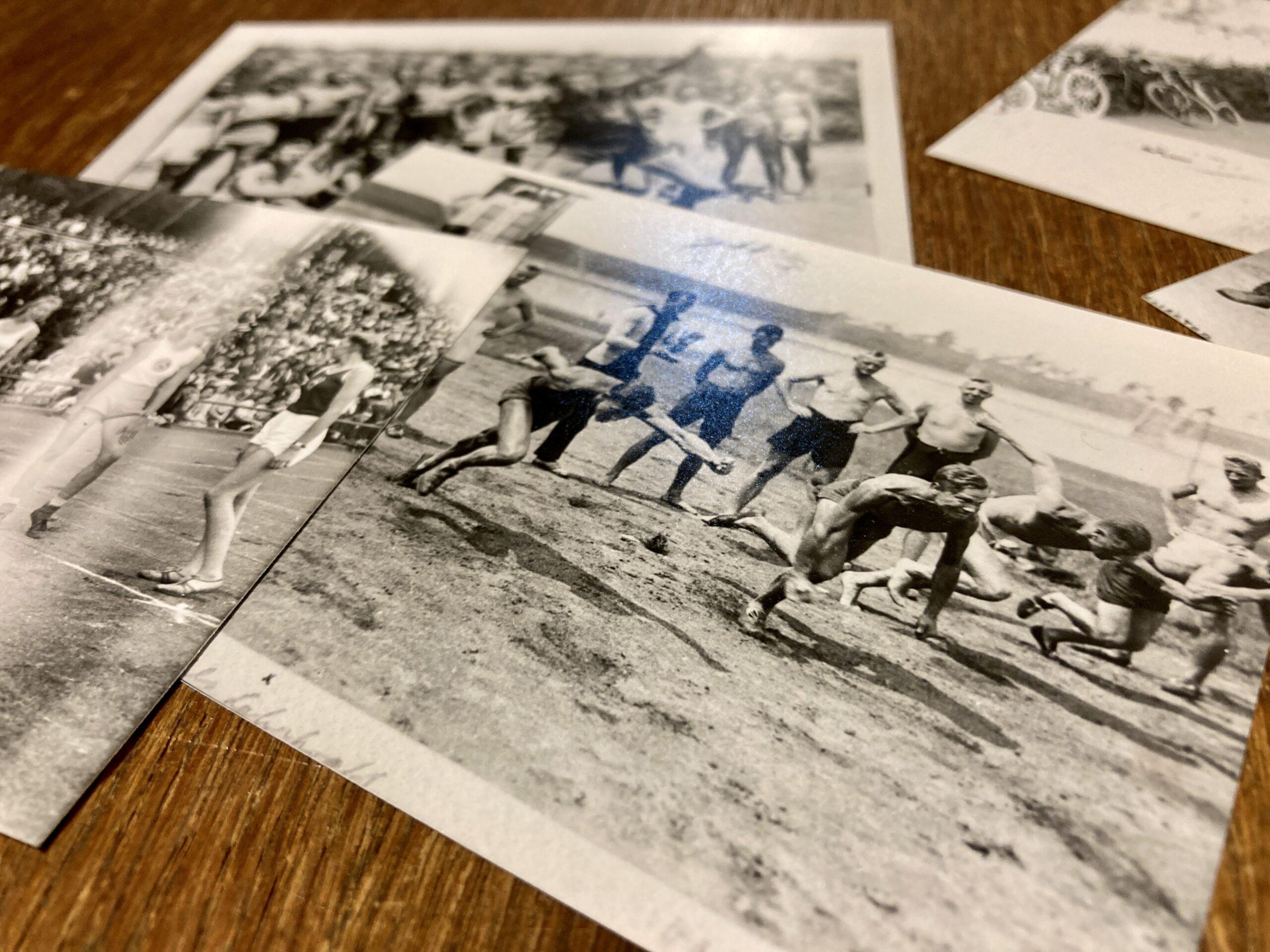 Mehrere schwarz-weiß Fotos liegen übereinander auf einem Holztisch. Das Bild im Vordergrund zeigt mehrere Männer, die den Start eines Rennens verfolgen. Der Start der 5 barfüígen Läufer auf blankem Erdboden ist im Bild festgehalten.