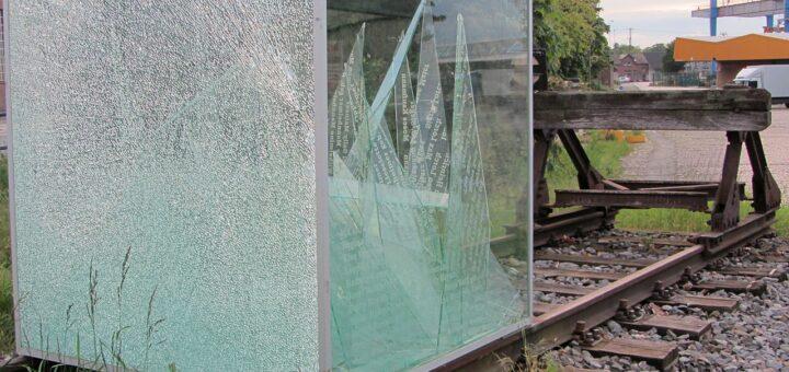 Das Bild zeigt das Denkmal Güterbahnhof: einen Glaskasten, in dem viele beschriftete Scherben liegen. Der Kasten steht auf einem Stupfgleis.
